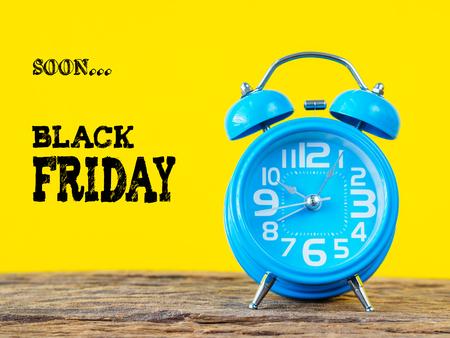 ブラックフライデータイムセールのコンセプト、黄色の背景を持つ青の目覚まし時計。