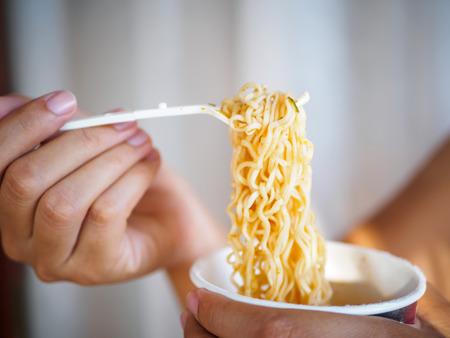 컵, 나트륨 다이어트 높은 위험 신부 실패에 매운 인스턴트 국수를 먹고 포크를 들고 손을. 건강 한 먹는 개념.