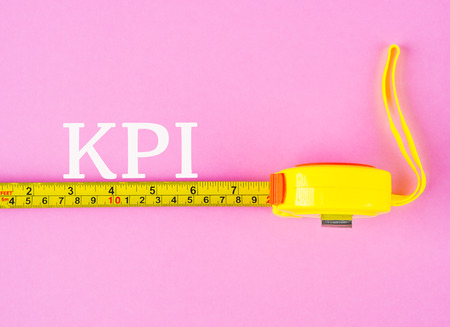 Closeup Of  a Measuring Tape With Key Performance Indicator Word Over Pink Background.
