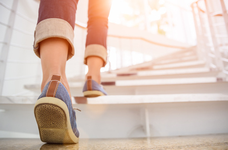 Young adult woman walking up the stairs with sun sport background. Imagens - 89681234