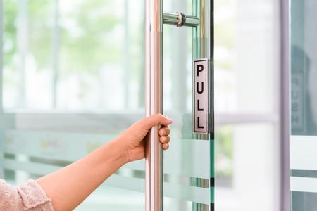 La mano de las mujeres del primer abre el botón de puerta. Foto de archivo