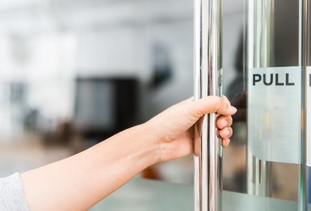 Zbliżenie kobiety ręka otwiera drzwiową gałeczkę.