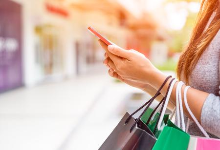 Mujer que sostiene los panieres que hacen compras en línea en su teléfono móvil en el supermercado. Foto de archivo - 89926425
