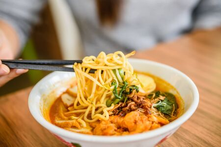 bean sprouts: Hand with Chinese chopsticks eating noodle, a famous Malaysia prawn noodle cerry soup. Stock Photo