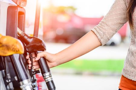 Close-up van vrouwenhand die een brandstofpomp houden bij een post.