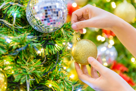 Woman hand decorating Christmas tree on bright bokeh background.