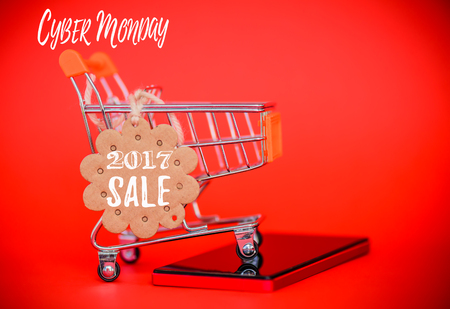 Cyber Monday sale concept, mini shopping cart with sale tag and mobile phone on red background