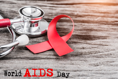 Rotes Bandbewusstsein und -stethoskop auf hölzernem Hintergrund für Welt-Aids-Tageskampagne. Standard-Bild - 91092767