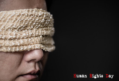 Closeup of a young woman with a blindfold in her eyes. Concept of censorship, freedom of speech, freedom of press. International Human Right day.