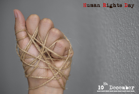 Woman hand tied with wire on dark background in low key. International human rights day concept. Imagens
