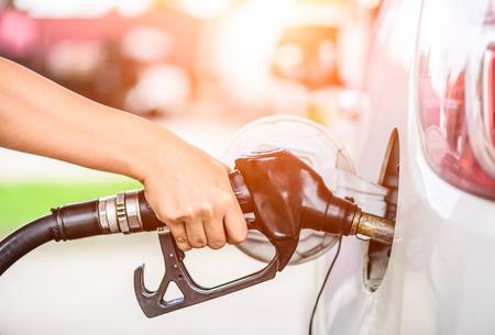 Zbliżenie trzyma pompę paliwową przy stacją kobiety ręka.