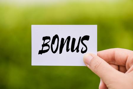 Hand holding Bonus card with green background. Business achievement concept. 版權商用圖片