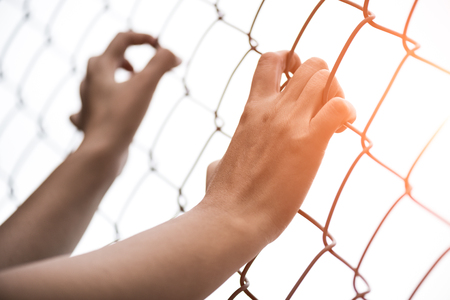 Woman hand holding on chain link fence for remember Human Rights Day concept. Stock Photo
