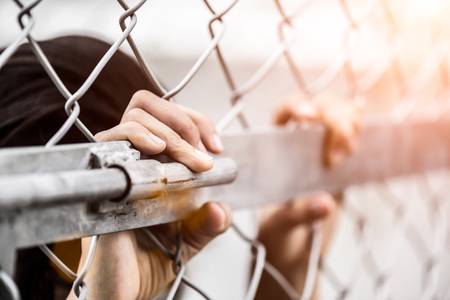 Woman hand holding on chain link fence for remember Human Rights Day concept. Banco de Imagens