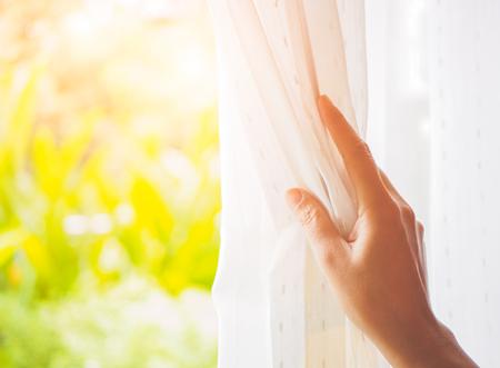 Die Hand der Frau, die Vorhänge im Schlafzimmer mit Hintergrund des natürlichen Lichtes und des Gartens öffnet.