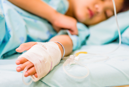 Closeup kid hand  sleeps on a bed in hospital with saline intravenous. 免版税图像 - 94147466