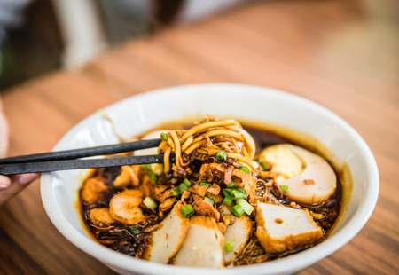 Soft focus hand with Chinese chopsticks eating noodle, a famous Malaysia Loh Mee.