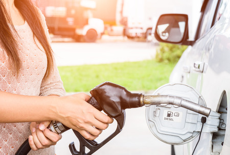 Woman pumping gasoline fuel in car at gas station. Stock Photo