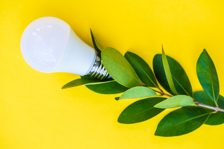 Light bulb on yellow background with green leaves Stock Photo