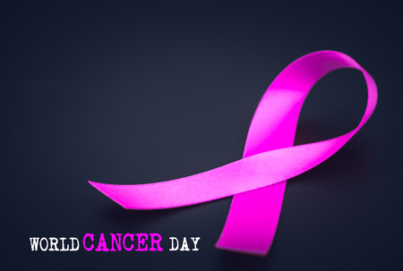 Purple ribbon awareness on black background  for World Cancer day. Stock Photo