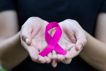Woman hands holding Purple CANCER awareness ribbon. Stock Photo