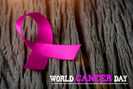 Purple ribbon on wooden background  for World Cancer day awareness campaign.