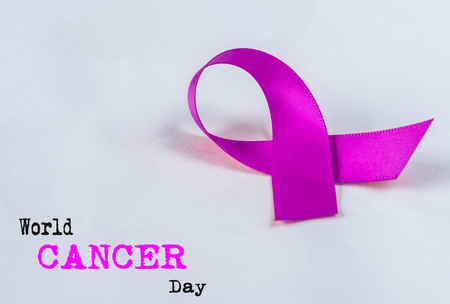 Soft focus Purple CANCER awareness ribbon on white background. World CANCER day concept.