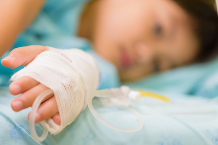 Closeup kid hand  sleeps on a bed in hospital with saline intravenous, selective focus. 版權商用圖片