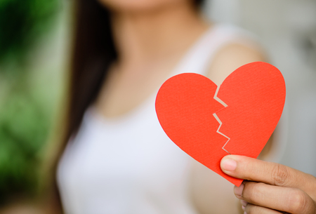 Young woman showing red ripped paper heart. Broken hearted on Valentines day concept. Stock Photo