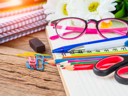 Colorful school supplies with books, color pencils, pink glasses, pen cutter and clips on wooden background. Back to school concept.