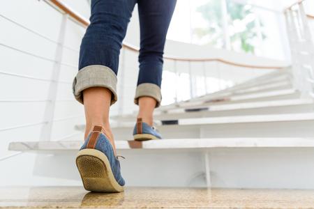 Junge erwachsene Frau, die herauf die Treppe mit Sonnensporthintergrund geht.