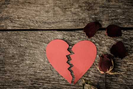 Top view dried red rose, dead red rose with red paper in shape of broken hearted on wooden background with vintage style. Broken hearted, Love, Wedding and Valentines day concept. Stock Photo