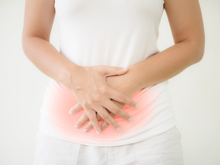 Woman having a stomachache, or menstruation pain with white background. Health care and medical concept. Stock Photo