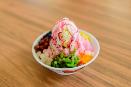 Soft focus of Ais Kacang topped with basil seeds, peanuts, corn, and a scoop of ice cream. Ice kacang literally meaning