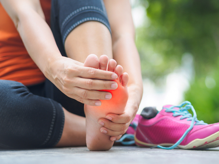 Woman suffering from an ankle injury while exercising.  Running sport injury concept. 版權商用圖片