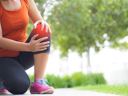 Runner sport knee injury. Woman in pain while running in the garden. Stockfoto