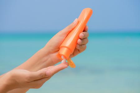 Frauenhand wenden Lichtschutz / sunblock auf dem Strand mit grünem Meer und blauem Himmel im Hintergrund an. Ferien und Entspannung, Sommerreisekonzept.