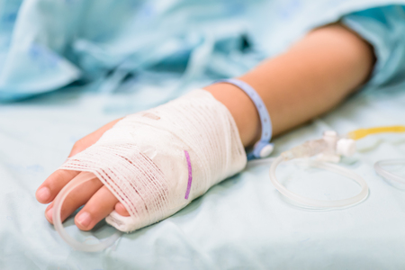 Closeup kid hand  sleeps on a bed in hospital with saline intravenous, selective focus. Stock Photo - 96733644