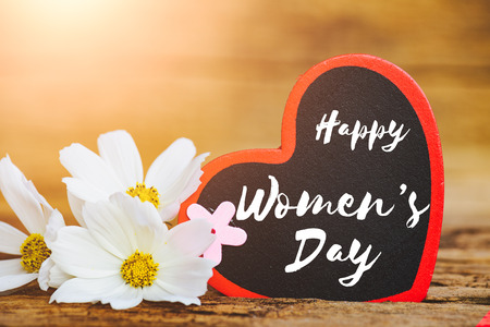 8 March Happy Women's Day message on wooden background with handmade red heart and white and purple flowers. Womens Day concept.