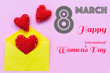 Happy Women's Day message on pink background with handmade red heart inside yellow letter. Womens Day concept.
