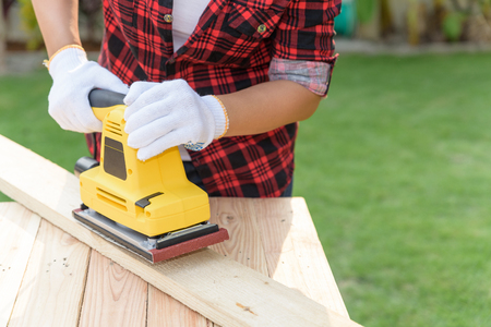 Womam Carpenter working with wood electrical sanding machine Stock Photo