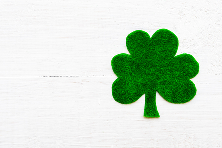 Happy St Patricks Day message on green paper clover and white wooden background Stock Photo