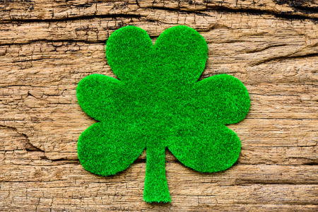Happy St Patricks Day message with green clover leaf on wooden background Stock Photo