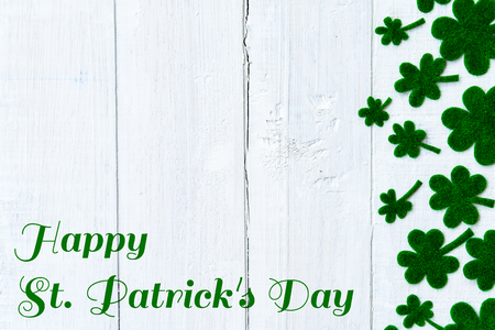 Happy St Patricks Day message and a lot of green paper clover leaf on white wooden background Stock Photo