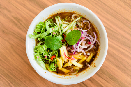 Laksa on wooden table. Laksa is a spicy noodle soup popular in the Peranakan cuisine. 版權商用圖片