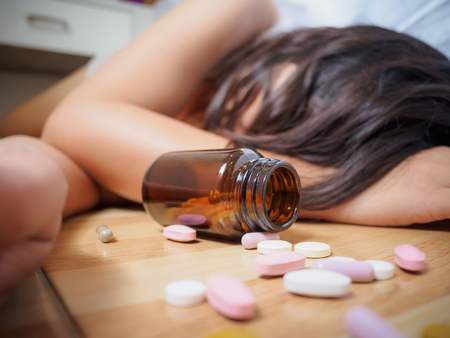 Young woman is lying on the floor with a lot of pills. Overdose and suicide concept. Stock fotó - 97667001