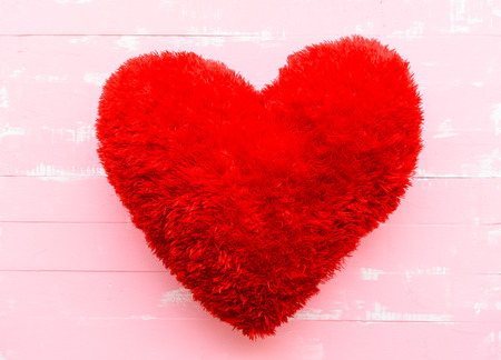 Beautiful big red pillow heart shape on white and pink wooden background. Love, Wedding and Valentines day concept.