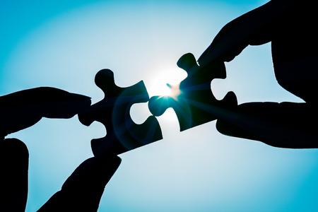 Silhouette der Hand der Nahaufnahmefrau, die ein Stück Puzzle über Sonnenlichteffekt verbindet. Symbol der Assoziation und des Verbindungskonzepts. Geschäftsstrategie.