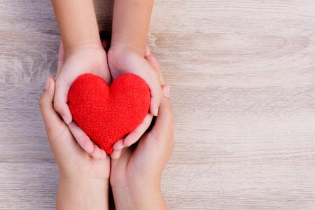 Gesundheitswesen, Liebe, Organspende, Familienversicherung und CSR-Konzept. Erwachsen- und Kinderhände, die handgemachtes rotes Herz auf hölzernem Hintergrund halten.