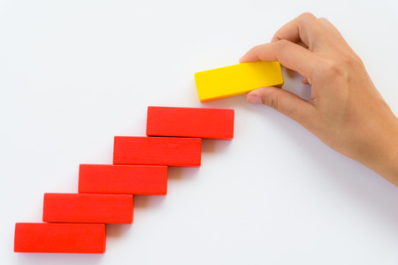 Concept of building success foundation. Women hand put yellow wooden block on red wooden blocks in the shape of a staircase